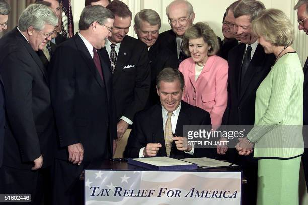 President George W Bush flanked by members of Congress signs the biggest tax cut in two decades into law a sweeping 135 USD trillion bill lowering US...