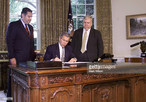 S President George W Bush flanked by Secretary of Energy Spencer Abraham left and Senior Economic Advisor Larry Lindsey signs an executive order...