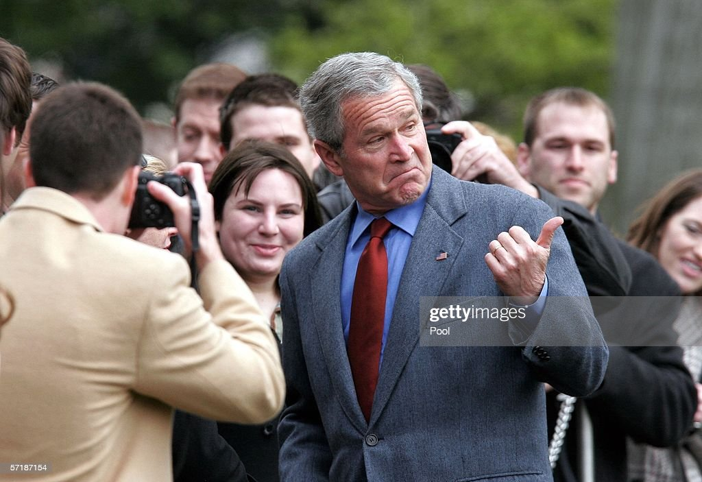 U.S. President George W. Bush gestures as he greets the crowd on the White House lawn after arriving at the White House March 26, 2006 in Washington, DC. President Bush spent his weekend at Camp David.