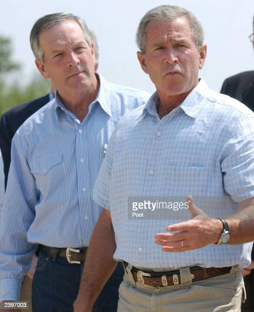 S President George W Bush gestures as he speaks with the media while US Commerce Secretary Don Evans listens at Bush's ranch August 13 2003 in...