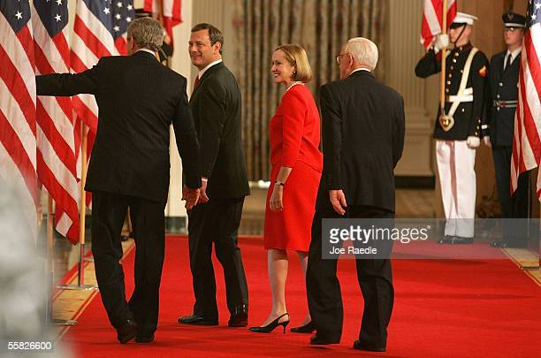 S President George W Bush gestures as he walks away with John Roberts his wife Jane Roberts and Associate Justice John Paul Stevens after Roberts was...