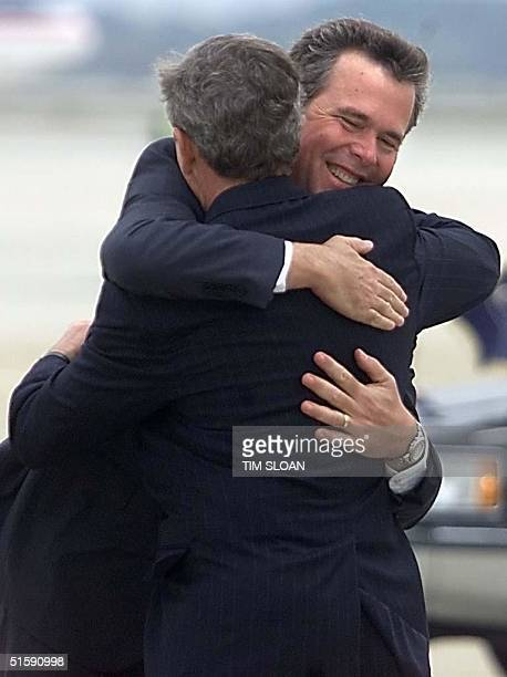 President George W Bush gets a hug from his brother Florida Governor Jeb Bush after arriving at Tyndall Air Force Base 12 March 2001 in Panama City...