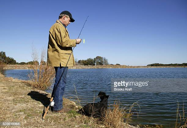 US President George W Bush goes fishing with his dog Barney on the lake of the Bush Ranch in Crawford Texas