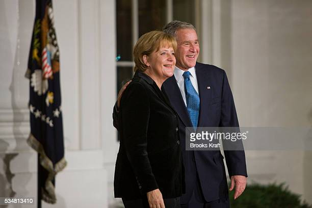 President George W Bush greets Chancellor Angela Merkel of Germany as she arrives at the North Portico of the White House in Washington President...