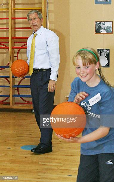 President George W. Bush grimaces as he plays basketball with children at Loughview integrated primary school on June 16 in Belfast as he ends his...