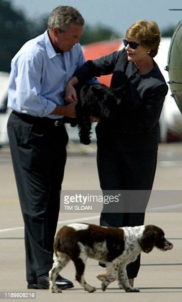US President George W Bush hands over dog Barney to First Lady Laura Bush as their other dog Spot walks by before they board Air Force One for the...
