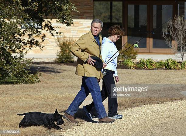 US President George W Bush heads off for a walk with his wife and First Lady Laura Bush and dog Barney from their home on the Bush Ranch in Crawford...