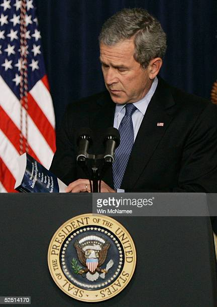 S President George W Bush holds a copy of a presidential commision's report on prewar intelligence on weapons of mass destruction during a speech...
