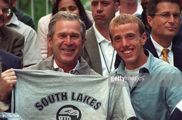 US President George W Bush holds a South Lakes High School Tshirt given him by Alan Webb during a Tee Ball event on the south lawn of the White House...