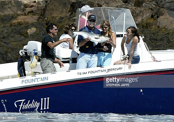 President George W Bush holds a stripped bass that his daughter Jenna caught off the coast of Kennebunkport Maine 07 August 2004 Bush was accompanied...