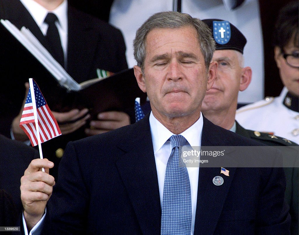 U.S. President George W. Bush holds an American flag during a Memorial Service at the Pentagon October 11, 2001 in Arlington, Virginia.