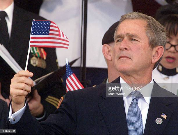 S President George W Bush holds an American flag during a Memorial Service for the victims of the terrorist attack October 11 2001 at the Pentagon in...