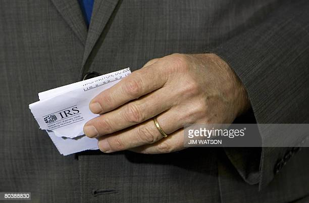 US President George W Bush holds an Internal Revenue Service mailer that was sent out to citizens explaining the benefits of the Economic Stimulus...