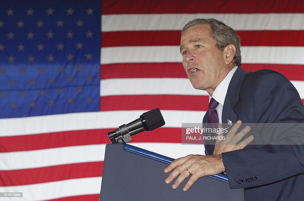 US President George W. Bush holds his hand on his : News Photo