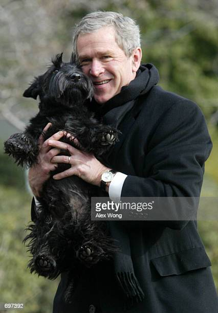 S President George W Bush holds up his dog Barney as he walks toward his residency from Marine One upon his arrival at the South Lawn of the White...