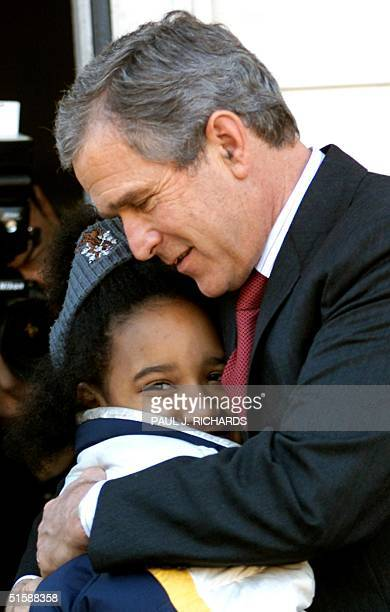 President George W Bush hugs 9yearold Kailah Johnson an after school student who attends the faithbased Fishing school which provides a safe haven...