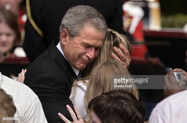 US President George W Bush hugs unidentified friends and family members of emergency personnel who died during the September 11 terrorist attacks at...