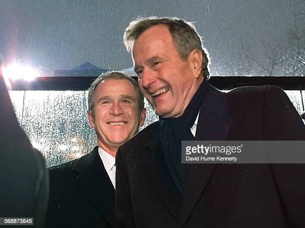 S President George W Bush in the Inaugural Parade stand in front of the White House jokes with his father former President George HW Bush during his...