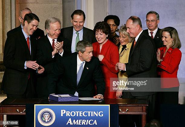 S President George W Bush is applauded after signing the intelligence reform bill by Sen Bill Frist 911 Commission Vice Chairman Lee Hamilton Sen Joe...