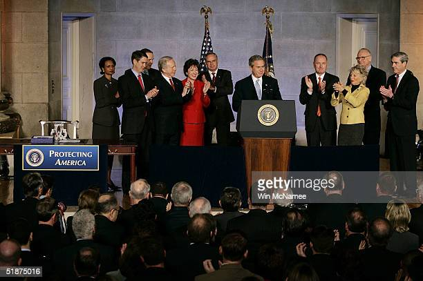 S President George W Bush is applauded before signing the intelligence reform bill by National Security Advisor Condoleezza Rice Sen Bill Frist 911...