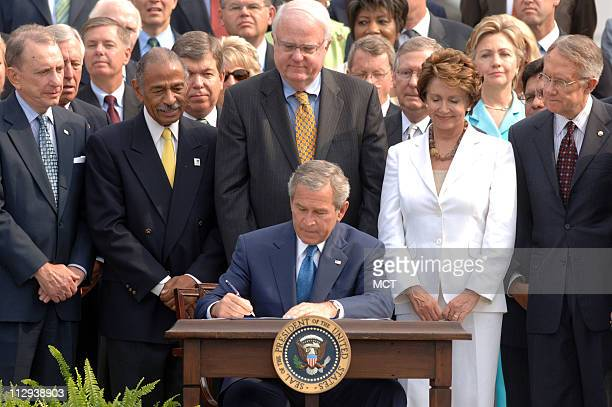 President George W. Bush is backed by members of the U.S. Senate as he signs a renewal of the Voting Rights Act during a ceremony on the South Lawn...