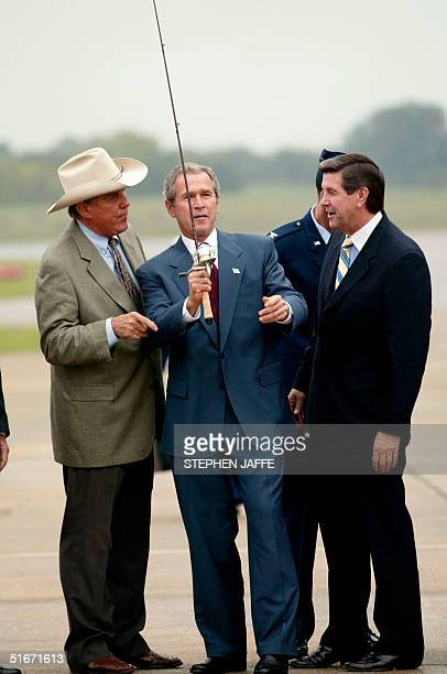 President George W Bush is given a fishing pole by Ray Scott as Alabama's gubernatorial candidate Bob Reilly watches at the airport 24 October 2002...