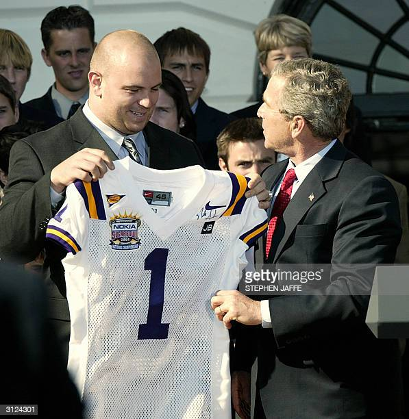 President George W Bush is presented a football jersey from Louisiana State University football player Rodney Reed on the South Lawn of the White...