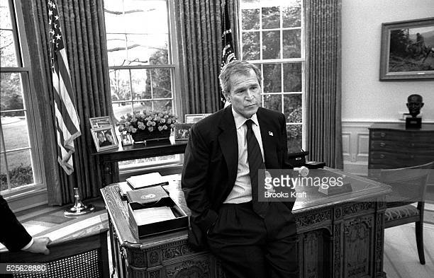 US President George W Bush is seen during a meeting with staff in the Oval Office at the White House