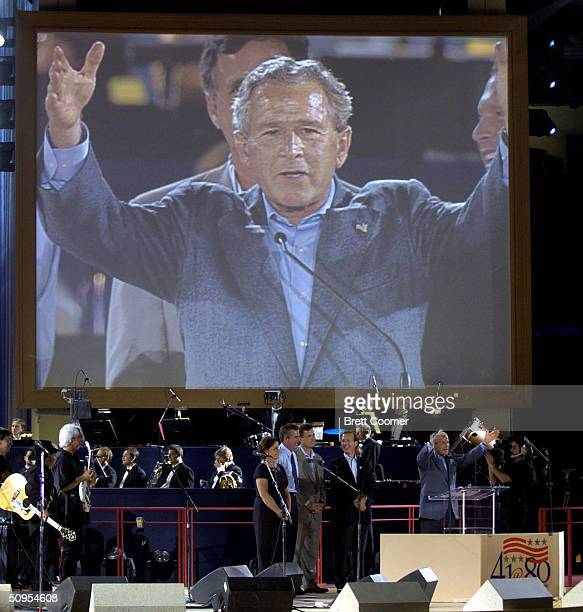 President George W Bush is shown on a giant video screen as he speaks about his father former President George HW Bush as his siblings Dorothy Jeb...