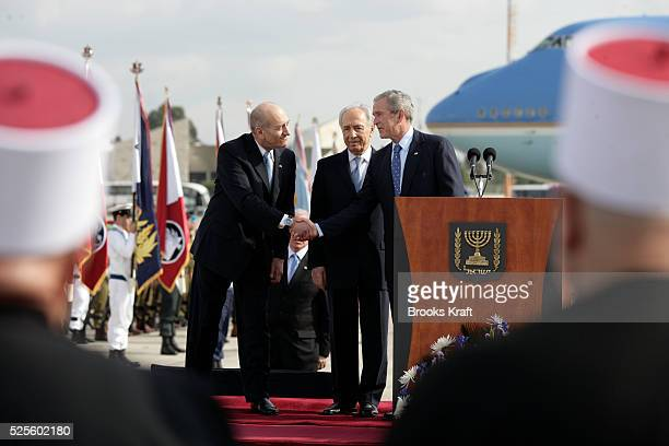 President George W Bush Israeli President Shimon Peres and Israeli Prime Minister Ehud Olmert during a state welcoming ceremony at Ben Gurion...