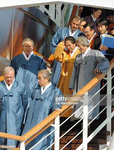 US President George W Bush Japanese Prime Minister Junichiro Koizumi and Peruvian President Alejandro Toledo talk while walking to attend the family...