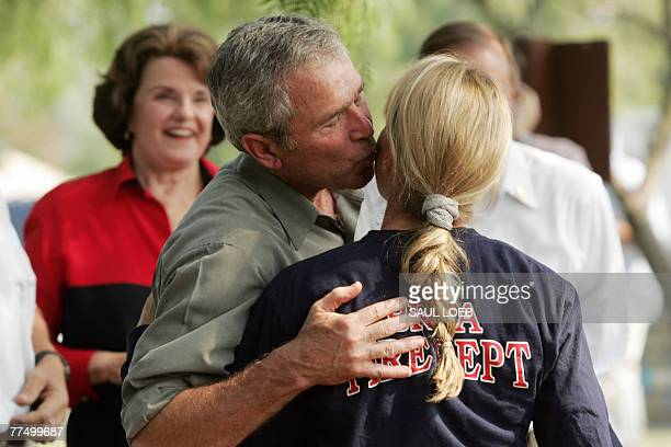 US President George W Bush kisses a first responder prior to having lunch with them while they fight the Southern California wildfires in Escondido...
