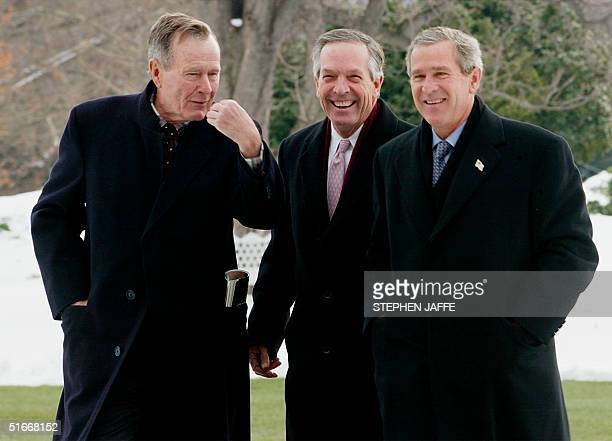 President George W Bush laughs with US Secretary of Commerce Don Evans and his father former US President George H Bush after arriving back to the...