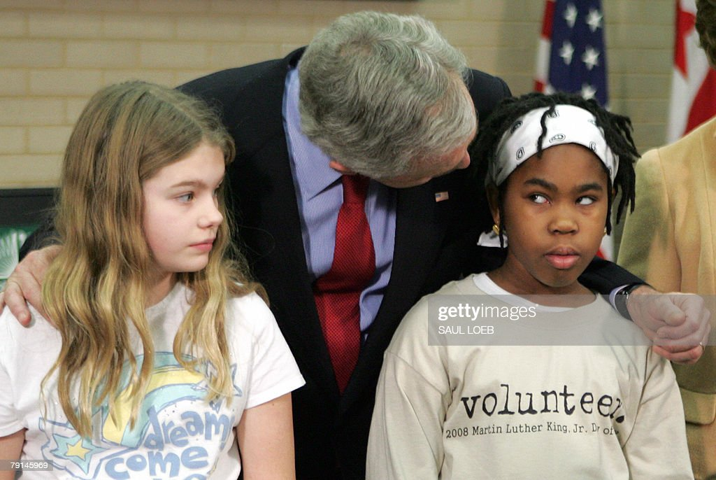 US President George W. Bush (C) leans over to talk with a girl (R) after Bush participated in a lesson for young children on the importance of Martin Luther King, Jr. Day during a tour of the Martin Luther King, Jr. Memorial Library in Washington, DC, 21 January 2008.