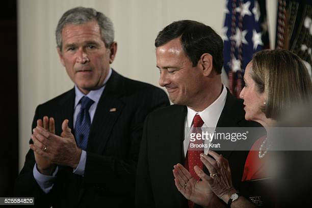 President George W. Bush, left, applauds as John Roberts, cemter, stands with his wife Jane after he was sworn in as the 17th chief justice of the...