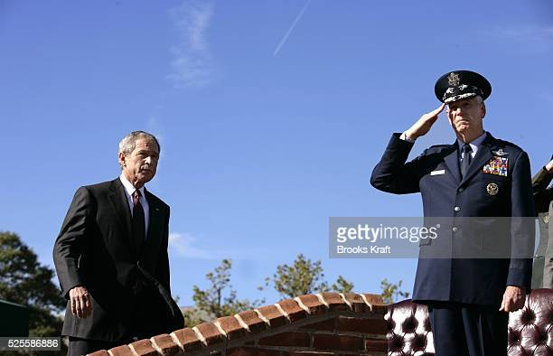 President George W. Bush, left, arrives to participate in the Armed Forces Farewell Tribute in Honor of General Richard B. Myers, right, and Armed...