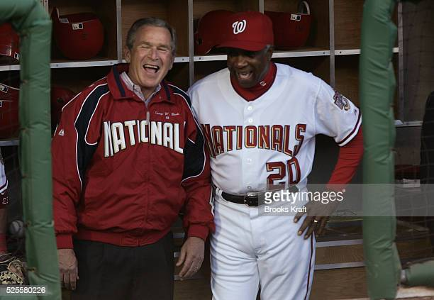 US President George W Bush left laughs with Manager Frank Robinson in the dugout before throwing out the first pitch for the home opener for the...