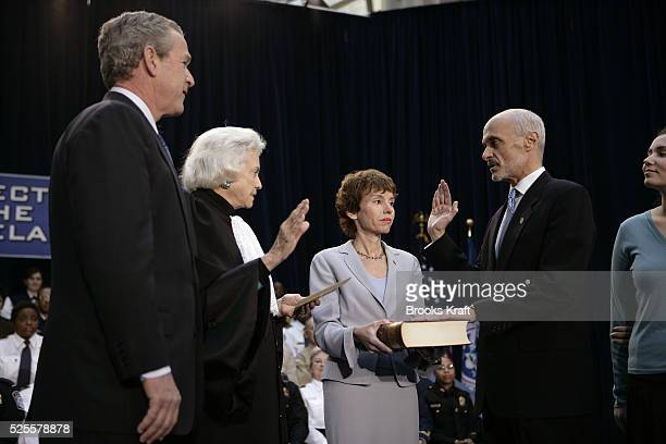 US President George W Bush left looks on as new US Department of Homeland Security Secretary Michael Chertoff right is swornin by US Supreme Court...