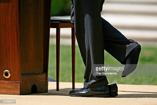 President George W Bush lifts his foot out of his shoe during a news conference in the Rose Garden of the White House May 24 2007 in Washington DC...