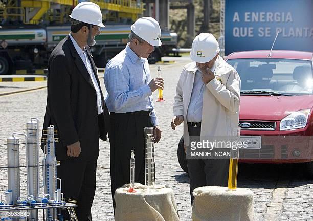 President George W. Bush looks a sample of bio diseal with Brazilian President Luiz Inacio Lula da Silva and Petrobras CEO Sergio Gabriella during a...