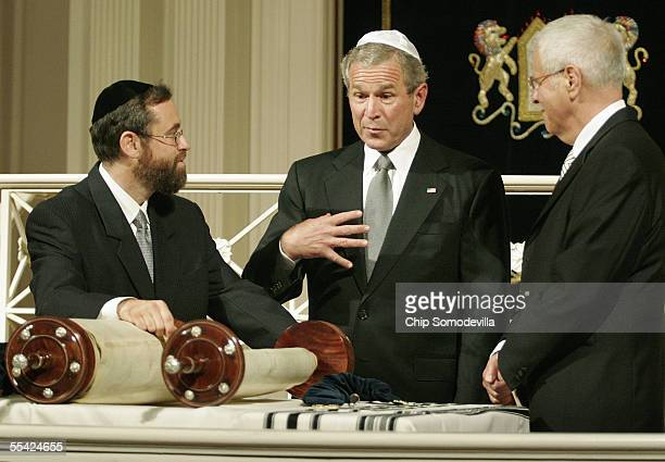 S President George W Bush looks at a Torah saved during the Holocaust with Rabbi Zvi Teitelbaum and Shelton Zuckerman synagogue vice president at...