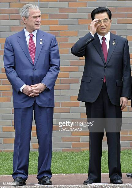 President George W. Bush looks on as Chinese President Hu Jintao adjusts his glasses as they arrive to pose for a family photo with other leaders...