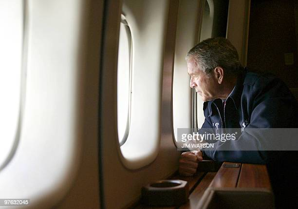 US President George W Bush looks out the window of Air Force One 31 August as he flies over New Orleans Louisiana surveying the damage left by...