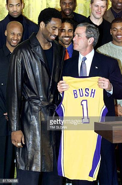 President George W Bush looks up as he is presented a team jersey from Kobe Bryant and the World Champion LA Lakers during an event in the East Room...