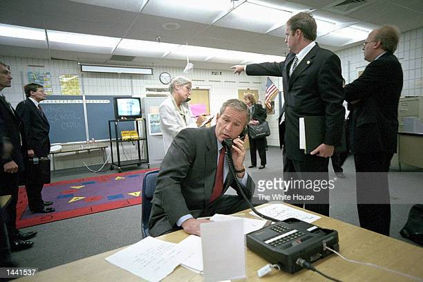 President George W. Bush makes a telephone call as White House Director Of Communications Dan Bartlett points to video footage of the terrorist...