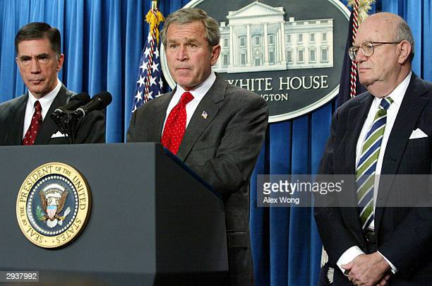 S President George W Bush pauses while speaking to the media as former Sen Chuck Robb and Judge Laurence Silberman listen February 6 2004 at the...