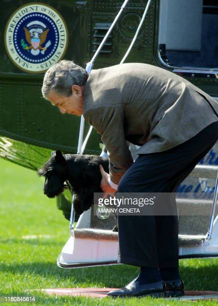 US President George W Bush picks up his pet dog Barney as it blocks his path disembarking from Marine One on the South Lawn of the White House 06...