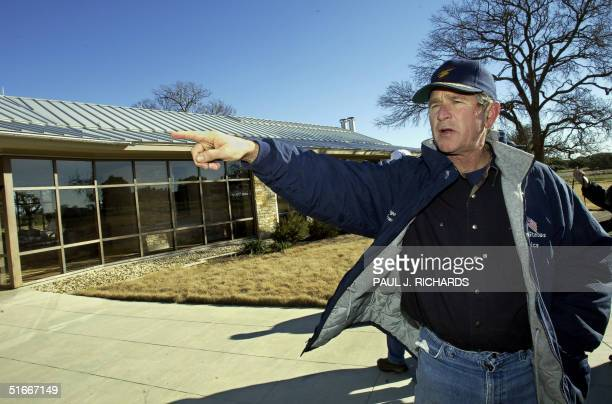President George W Bush points out features of his Texas house after the President took reporters on a tour and brisk 4 mile walk of his approx 1600...