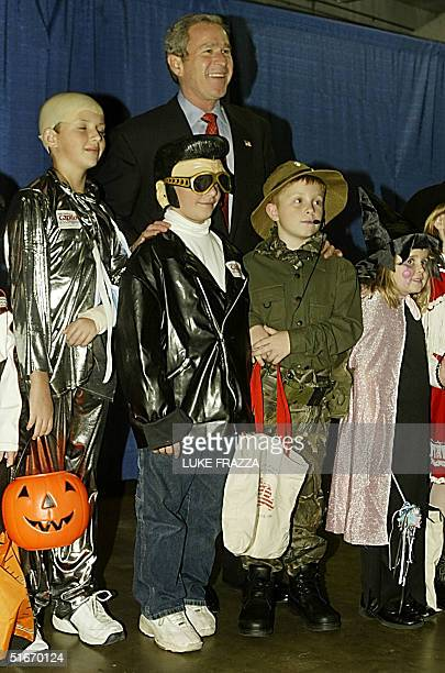 President George W. Bush poses with children dressed in Halloween costumes at a campaign rally at Charleston Civic Center Charleston, West Virginia...