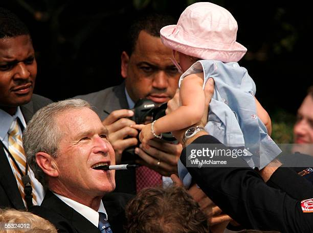 S President George W Bush reaches up to lift a toddler into the air from a family member at the 9/11 Heroes Medal of Valor Award Ceremony September 9...